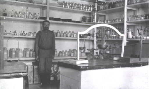 <p>A member of the medical personnel staff stands in front of the shelves in the dispensary at Military Hospital No. 16.</p>