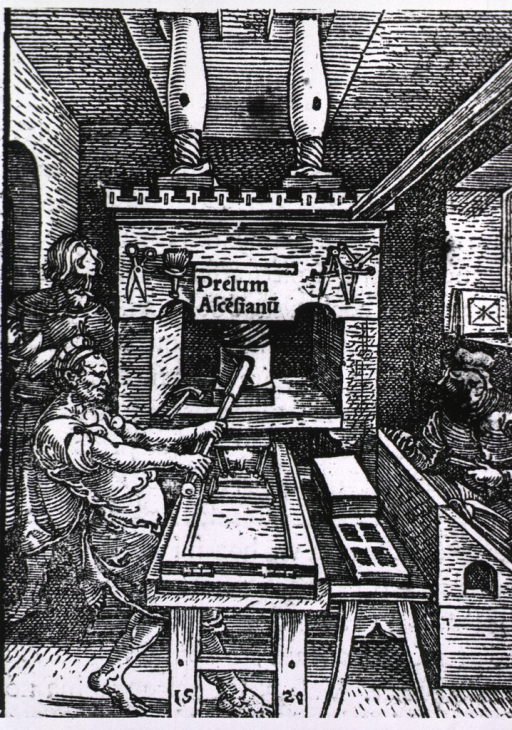 <p>Interior of printing shop, with press being used in foreground.</p>