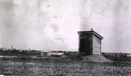 <p>A view of a latrine with one of the two doors open.</p>