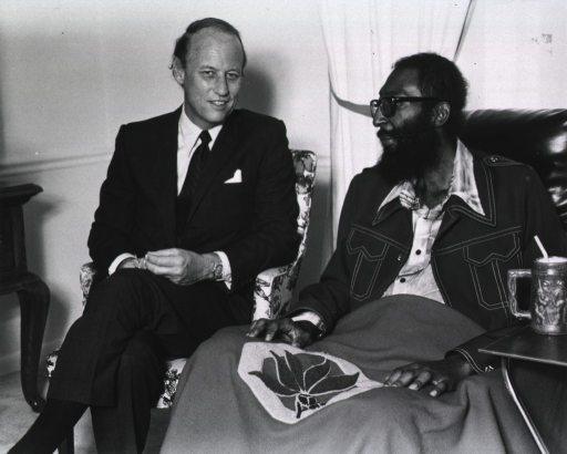 <p>Dr. Donald S. Fredrickson, director of the National Institutes of Health (NIH) is seated beside a man who sits in an padded chair.  The man has a blanket over his legs, a hospital band on his right arm, and a standing portable tray with a mug and straw next to him.   A gathered window curtain is between Dr. Fredrickson and the man.</p>