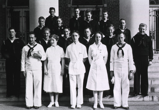 <p>Exterior view: medical staff and Coast Guardsmen in uniform stand on the steps to the hospital building.</p>