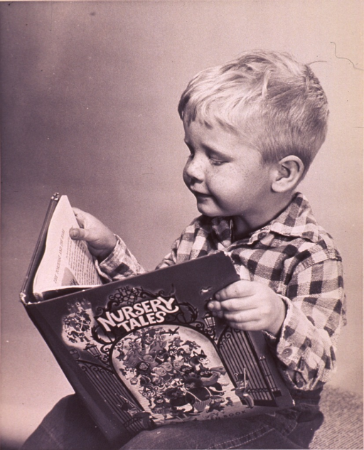 <p>A child reading a book of nursery tales.</p>