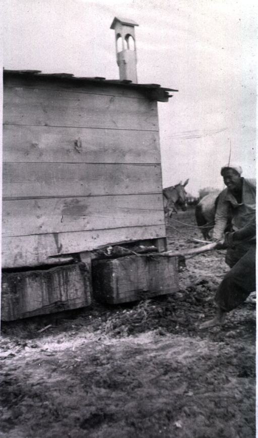 <p>A man pulls out one of the two waste containers from under the back of a latrine.</p>