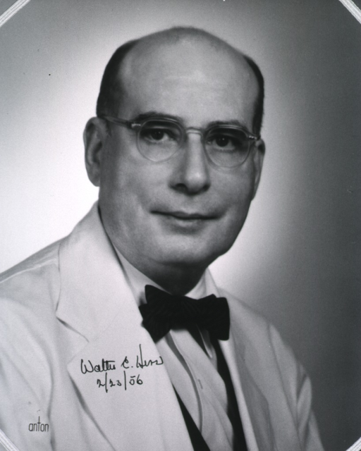<p>Head and shoulders, right pose, full face; wearing lab coat and glasses.</p>