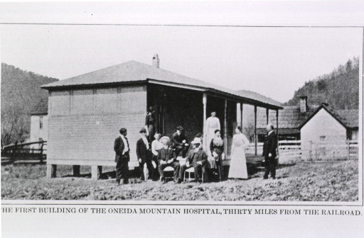<p>Exterior view of a small wooden building with several people standing and sitting by the porch.</p>