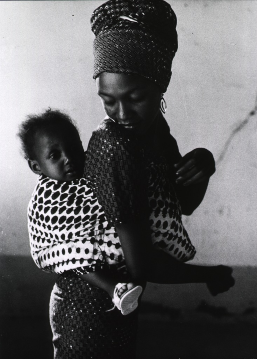 <p>A young woman is carrying a small child on her back.</p>