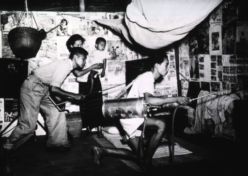 <p>Interior view: a man is spraying the inside of a dwelling at the direction on another man; a woman holding a child is standing in the background observing.</p>