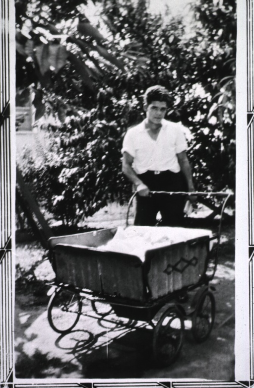 <p>Young man pushing baby carriage with twins.</p>