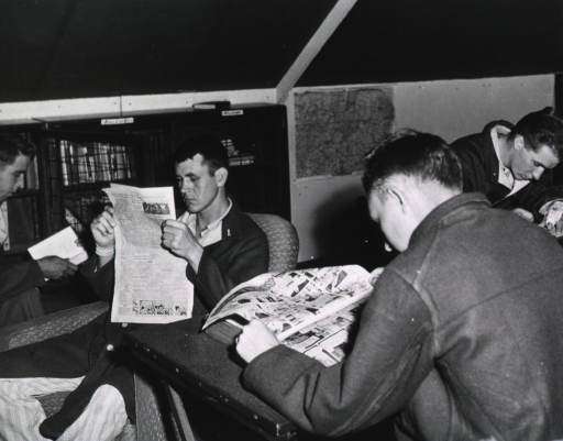 <p>Several servicemen sit in chairs and read books and newspapers.</p>