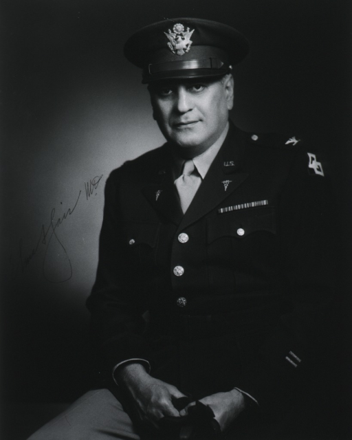 <p>Three-quarter length, seated, full face; wearing uniform and cap (Colonel); holding gloves.</p>
