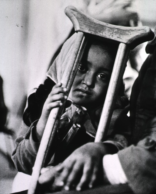 <p>A young girl shown half-length; her face is framed by a pair of crutches which are resting against her head.</p>