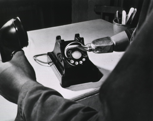 <p>The photograph is taken so that only the arms of a man are visible, the view being from the vantage point from behind the left arm.  The right arm is prosthetic, with the hook in the process of dialing a telephone.  The left hand holds the receiver.  The table is otherwise clear except for a glass containing a brush, a pencil, and other implements.</p>