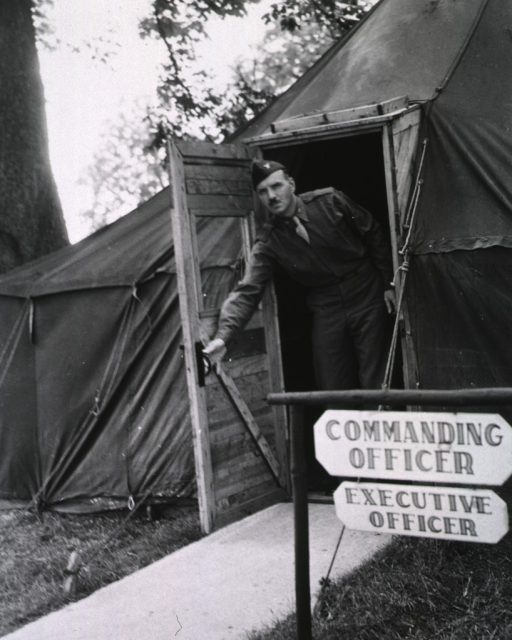 <p>Col. Zellhoefer is shown opening the door of his tent.  Two signs reading &quot;Commanding Officer&quot; and &quot;Executive Officer&quot; are posted in front of the tent.</p>
