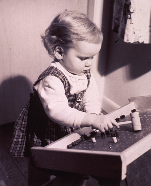 <p>A little girl is playing with a peg board.</p>