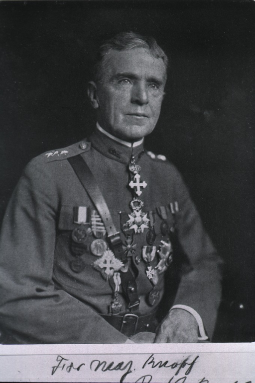 <p>Seated, wearing medals and citation emblems.</p>