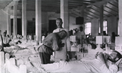 <p>A physician checks a patient in a ward at Military Hospital No. 11; other patients are in their beds.</p>