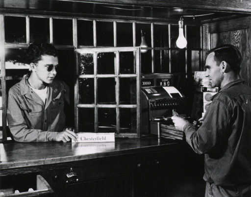 <p>A man wearing dark glasses leans through a window in a store and pushes a box labelled &quot;Chesterfield&quot; toward a cashier.  The cashier holds dollar bills above an opened cash register.</p>