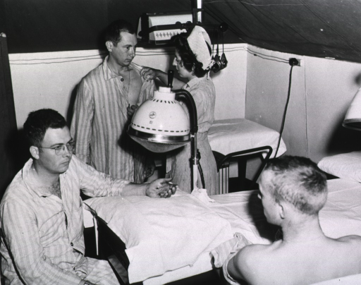 <p>Two servicemen sit next to a hospital bed, while a third stands and is examined by a nurse.</p>