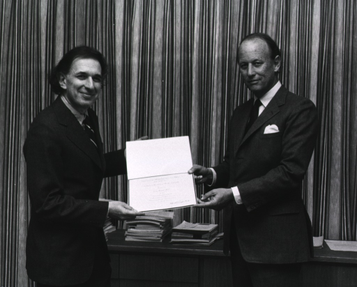 <p>Eric R. Kandel, director of the Center for Neurobiology and Behavior at Columbia University, is standing with Donald S. Fredrickson, director of the National Institutes of Health (NIH).  They are holding an award.  Behind them is a long, narrow table with piled journals and papers.  A stage-type curtain is in the background.</p>