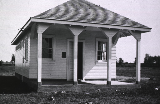 <p>Exterior view of the &quot;white house&quot;; front view of small rectangular building showing porch and entrance to the public privy.</p>