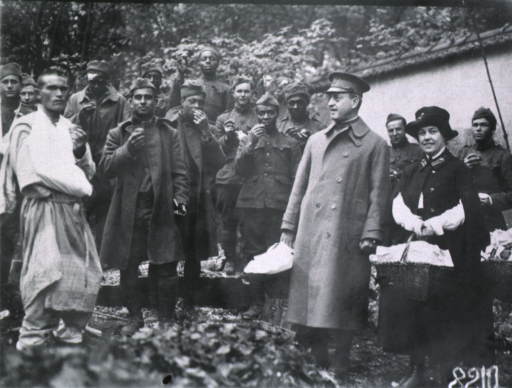 <p>Full length, standing, left pose; wearing over-coat and cap; with large group of soldiers/patients and a Red Cross nurse.</p>