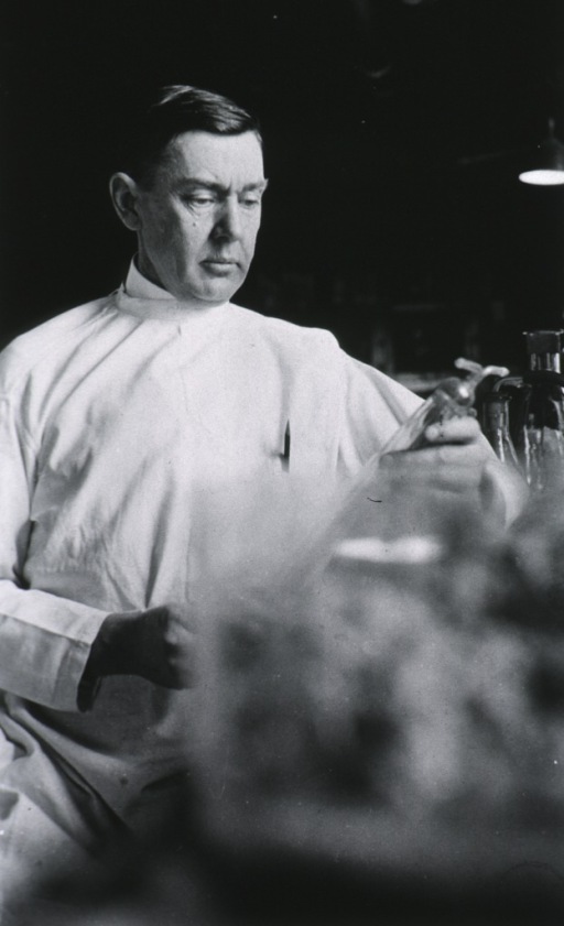 <p>Three quarter length, seated at laboratory table, wearing white lab coat.</p>