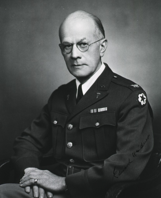 <p>Seated, full face, hands in lap, uniform, colonel.</p>