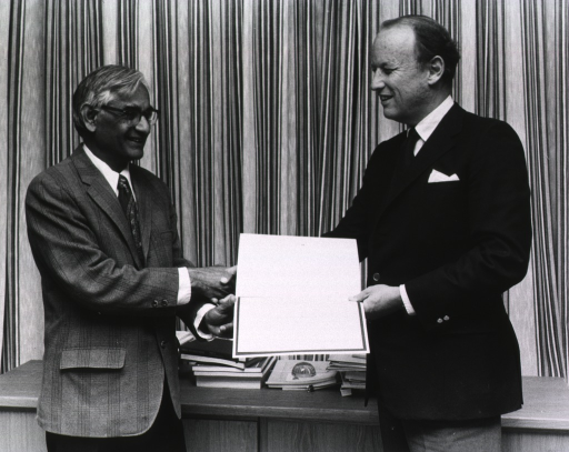 <p>Har Gobind Khorana, Alfred Sloan Professor of Biology and Chemistry at the Massachusetts Institute of Technology, and Donald S. Fredrickson, director of the National Institutes of Health (NIH) are shaking hands while holding the NIH lecture award.  They are standing in front of a cradenza which is piled with books, journals, and papers.  In the background is a curtain.</p>