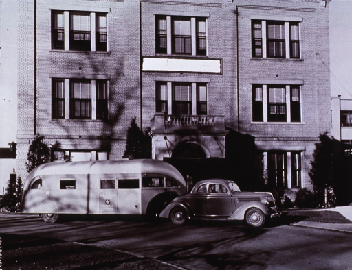 <p>Exterior view: Trailer and passenger car are parked in the circular driveway of a building.  On the side of the trailer is printed: U.S. Public Health Service, Hospital Division.</p>