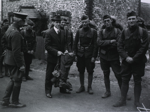 <p>Somewhere-in-England, while inspecting American Red Cross activities, Secretary Baker decides to try on an enlisted man's pack.  Also shown are a group of enlisted men and Col. Samuel Jones.</p>