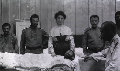 <p>A consultation among physicians and a nurse beside a patient.</p>