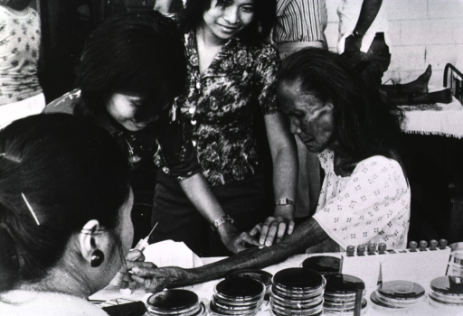 <p>An old woman is sitting with her left arm extended and resting on a table; two young girls hold a cotton ball on the woman's arm, one of the girls is holding a syringe; there are many Petri dishes on the table.</p>