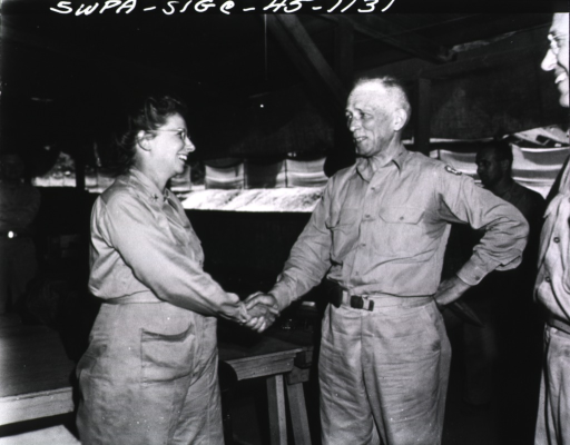 <p>Major Kirby shakes the hand of Major General Kirk inside military headquarters.  Several stand and watch the meeting.</p>
