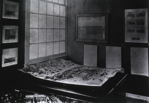 <p>Three-dimensional table-top model of a landscape depicting fields, mountains, houses, and trees; the model appears to be part of a larger museum exhibition, possibly at the Jamestown Ter-centennial Exposition, 1907.</p>