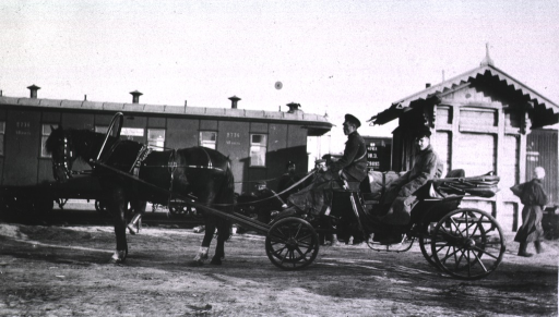 <p>The chauffeured battery surgeon's wagon stands beside the train at Harbin.</p>