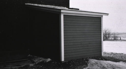 <p>Exterior view showing small wooden structure attached to a brick building; apparently a water pump facility is housed within this wooden building.</p>