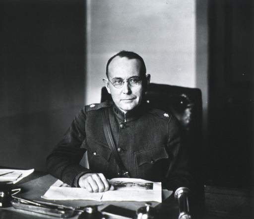 <p>Half-length, seated at desk, full face; wearing uniform and glasses; hand on desk.</p>