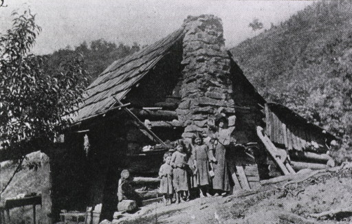 <p>Exterior view of a log cabin on a hillside; a woman and four children are standing by a stone chimney.</p>
