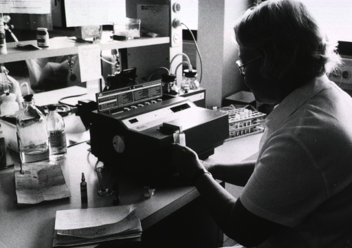 <p>A technician is sitting in a laboratory; she is using a piece of equipment that may analyze blood samples.</p>