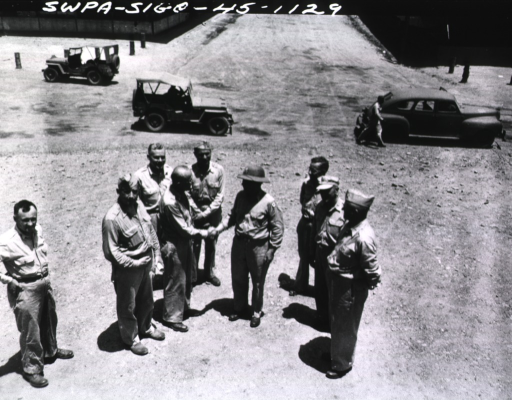 <p>The major general shakes hands with a military personnel, while eight other military personel either watch them or the camera.  In the background are three military vehicles, including two jeeps.</p>
