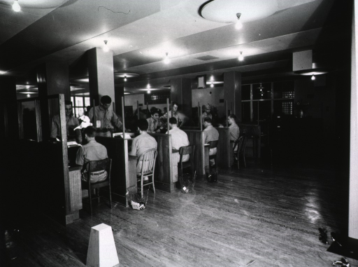 <p>Servicemen sit at desks in cubicles with their backs to the camera.  Facing each of the men is another serviceman.  The low-ceilinged room is lit by numerous bare light bulbs.</p>