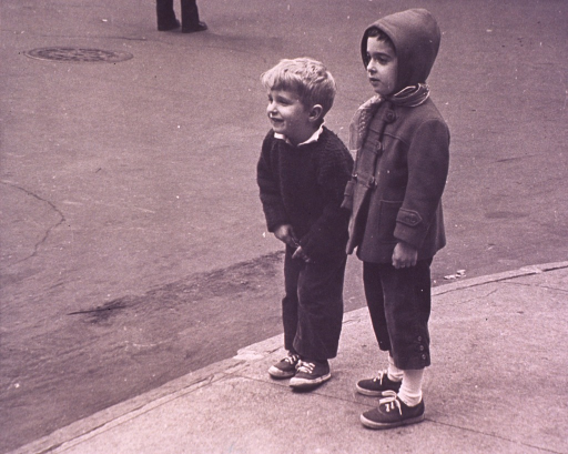 <p>Two children are standing on a sidewalk.</p>