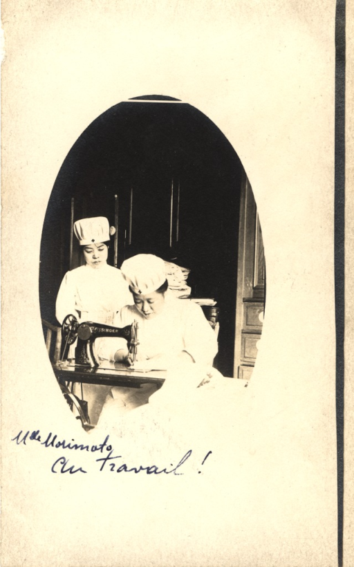 <p>Postcard featuring a black and white photograph of an Asian nurse who is sewing with a Singer sewing machine. She is dressed in white and has a white hat with a dark cross on it. There is also another nurse behind her, who is wearing the same uniform.</p>