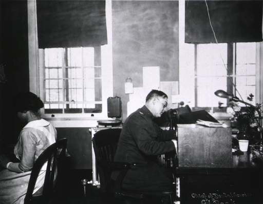 <p>Seated at desk, working, in uniform.</p>