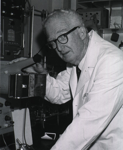 <p>Half-length, turned to left, wearing glasses and lab coat, shown in laboratory at electronic apparatus with camera attached.</p>