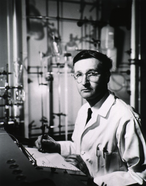 <p>Half-length, seated in laboratory, left pose, full face; wearing white lab coat, glasses; working on a graph.</p>