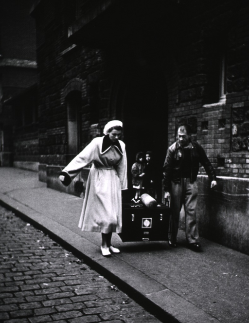 <p>Exterior view: a man and a woman are carrying a portable incubator; two children observe from the entryway to a brick and stone building.</p>