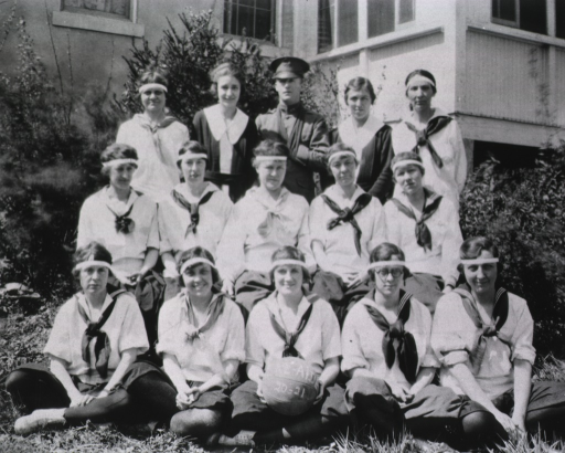 <p>Three rows of women in athletic uniforms pose for a picture in front of a building.  In the back row, a man in military uniform stands in the middle.  In the front row, which is seated on the ground, the woman in the middle holds a basketball on which is inscribed:  &quot;Re-AIDE 20-21.&quot;</p>