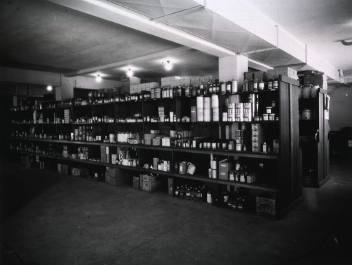 <p>Various supplies are stacked on shelves in a storeroom.</p>