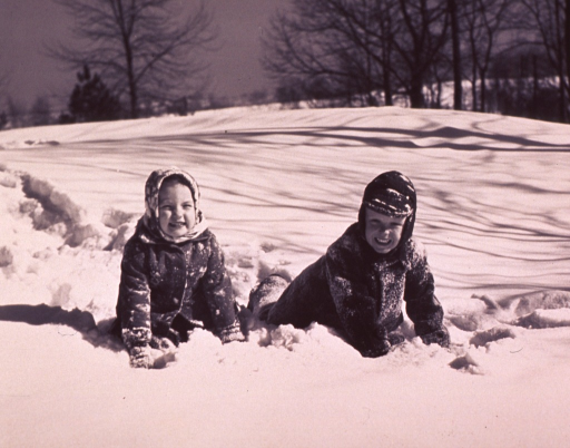 <p>Two children are playing in the snow.</p>